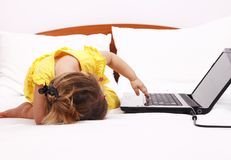Exhausted kid who try touch laptop. Exhausted kid who try touch keyboard of laptop Royalty Free Stock Images