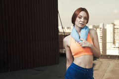 Exhausted lady with towel around neck at workout Stock Image