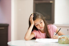 Exhausted little girl studying. Exhausted little girl while doing her homework Royalty Free Stock Photography