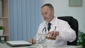 Exhausted male doctor allowing himself strong drink after hard working day. Stock footage stock video