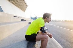 Exhausted male runner in fluorescent t- shirt taking break after workout training in sunrise time outdoors Stock Photos