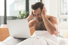 Exhausted male worker using laptop at home. Overworked. Tired young man feels terrible headache while working on computer. He is sitting on bed half naked and Royalty Free Stock Images