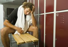 Exhausted man. Young, exhousted man sitting on bench in locker room with closed eyes. Holding towel on neck. Front view Royalty Free Stock Photography