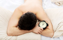 Exhausted man being awakened by an alarm clock. Royalty Free Stock Images
