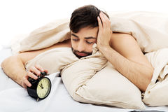 Exhausted man being awakened by an alarm clock. Royalty Free Stock Photography