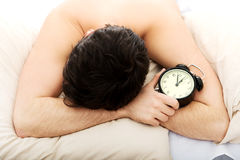 Exhausted man being awakened by an alarm clock. Stock Photo