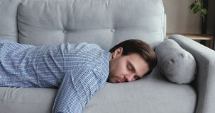 Exhausted man came home after work flopped down on sofa