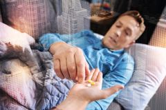 Exhausted man feeling unwell and taking pills from his son. Ill man. Serious calm tired men resting on the sofa and feeling unwell while taking necessary pills stock photo