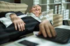 Exhausted man in office Royalty Free Stock Image