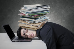 Exhausted man with paperwork on his head. Young businessman sleeping on the laptop computer with documents on his head Royalty Free Stock Photography