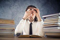 Exhausted man reading books Royalty Free Stock Image