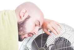 Exhausted man resting on blowing fan or cooler Royalty Free Stock Photo