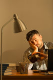 Exhausted man sitting at desk Stock Images