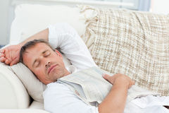 Exhausted man sleeping on the couch at home Royalty Free Stock Photos