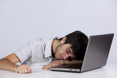 Exhausted man sleeping at his office. Young man sleeping next to his laptop computer (with gray background Stock Image