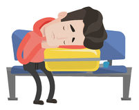 Exhausted man sleeping on suitcase at airport. Royalty Free Stock Image