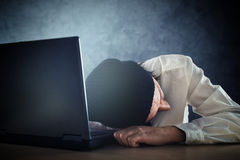 Exhausted man sleeps on laptop at office desk Stock Photography