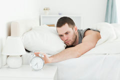 Exhausted man switching off his alarm clock Royalty Free Stock Photo
