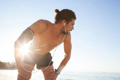 Exhausted man taking a break after jogging on beach Stock Photography