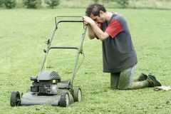 Exhausted Man With Lawn Mower Royalty Free Stock Photos