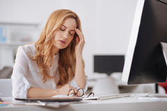 Exhausted manager suffering from chronic daily headaches in the office Royalty Free Stock Photo