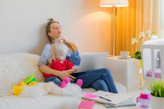 Exhausted mother fallen asleep in front of computer. While sitting with child royalty free stock image