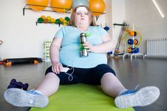 Exhausted Obese Woman Sitting on Mat. Full length portrait of tired obese woman sitting on yoga mat on floor and listening to music resting after fitness workout Royalty Free Stock Image