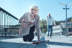 Exhausted older woman falling down with heart attack. Serious heart problems. Selective focus on a helpless senior lady standing on her knees and touching her Stock Photo