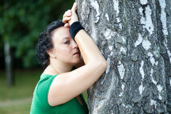 Exhausted overweight woman leaning on the tree Stock Images