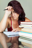 Exhausted and overworked hispanic woman. Studying with a pile of books on her desk Royalty Free Stock Photography