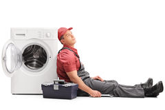 Exhausted plumber sitting by a washing machine Stock Images