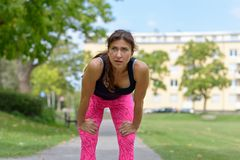 Exhausted runner leaning over with hands on knees. Exhausted female runner wearing pink sweatpants and black tank top leaning over with hands on knees in park royalty free stock image