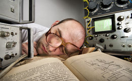 Exhausted scientist sleeping on book Royalty Free Stock Photography