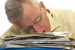 Exhausted senior businessman. An exhausted senior businessman has fallen asleep on his work stock images