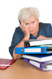 Exhausted senior lady with paperwork. Exhausted senior lady leaning on her elbow with a dejected look alongside a huge stack of files and paperwork Stock Images