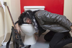 Exhausted senior male guitarist sleeping in toilet Stock Photos