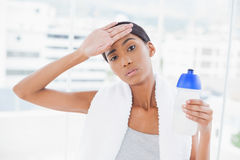 Exhausted sporty model wiping her forehead after exercising Royalty Free Stock Image
