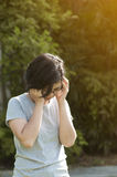Exhausted, streesed  Illness and tired concept. Asian glasses woman having headache while workout at the park. Natural background Stock Image