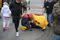 LONDON, UK - February 16, 2018: Exhausted street artist next to his fancy dress counting hard earned money, people walking and loo royalty free stock images