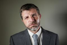 Exhausted and stressed businessman in suit and tie feeling tired and bored in overwhelmed and frustrated face expression stock photo