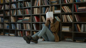 Exhausted student covering her face with book stock video