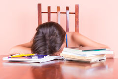 Exhausted student  sleeping with her head on a table Stock Photo