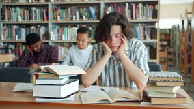 Exhausted teenager touching face then studying in university library at desk. Exhausted student teenager is touching face then studying reading books taking stock video