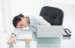 Exhausted stylish brunette businesswoman sleeping on her desk Royalty Free Stock Photography
