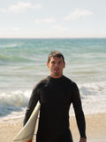 Exhausted surfer after session. An exhausted surfer coming in from a wild session. Tongue hanging out of his mouth expressing exhaustion Royalty Free Stock Image