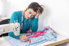 Exhausted Tailor Leaning On Workbench. Exhausted female tailor leaning on workbench in sewing factory Royalty Free Stock Image