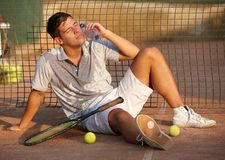 Exhausted tennis player on ground. Exhausted male tennis player sitting on ground after tennis game, refreshing, cooling himself Royalty Free Stock Photography
