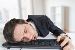 Exhausted or tired businessman is sleeping on keyboard in office Stock Images