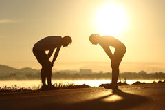 Exhausted and tired fitness couple silhouettes at sunset. Side view of a exhausted and tired fitness couple silhouettes at sunset stock photo