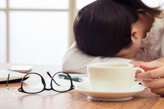 Exhausted and tired young businesswoman sleeping on desk. Exhausted and tired young businesswoman holding coffee and sleeping on desk Stock Image